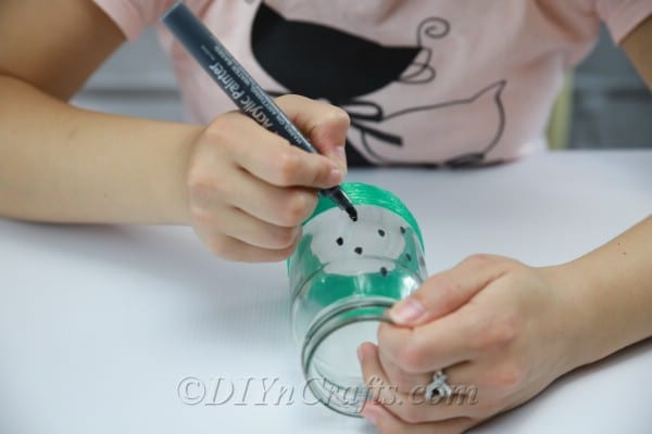 Continue drawing watermelon seeds all around your jar.