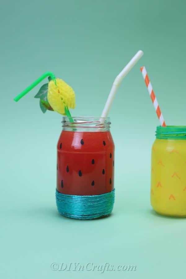 Fruit-painted jars with straws sit against a plain backdrop.