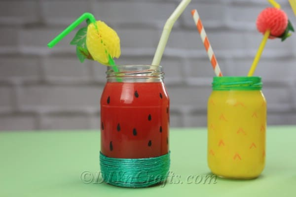 Fruit themed drink jars for summer rest on a green table.