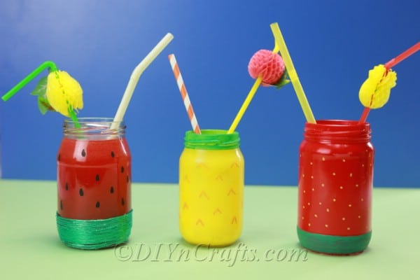 Summer fruit jars with straws are displayed against a blue backdrop.
