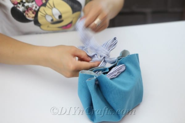 Pull on the ends of the scarf to close the bag.