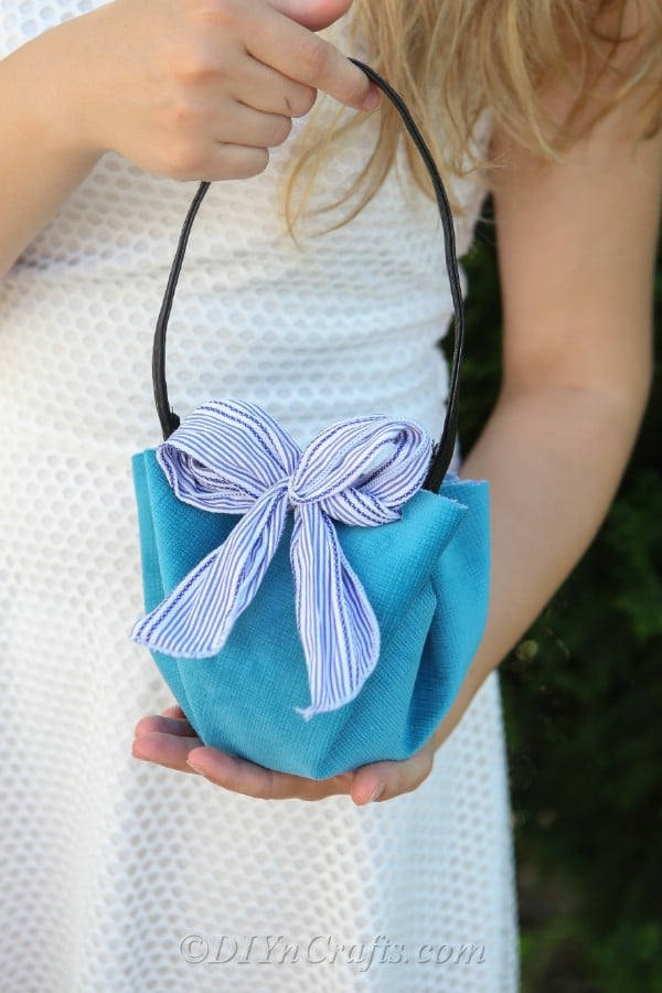 A woman holding a DIY handbag.
