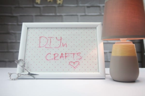 "A handcrafted whiteboard reads ""DIYnCrafts."""