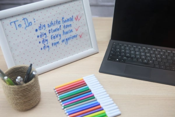 A decorative DIY whiteboard next to a laptop and a set of colorful markers.
