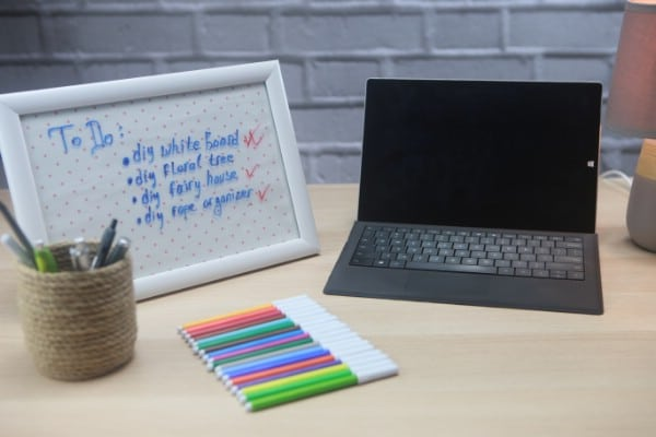 A handcrafted whiteboard sits next to a computer and colorful markers.
