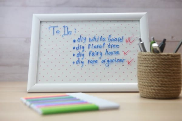 A decorative whiteboard sits on a desk with colorful markers.
