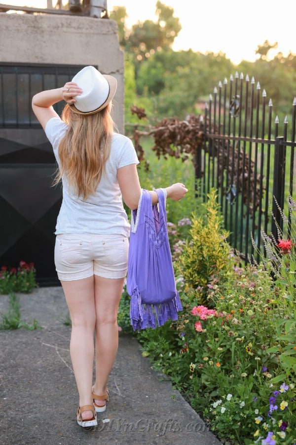 A woman walks in a garden with a bag made from an old T-shirt.