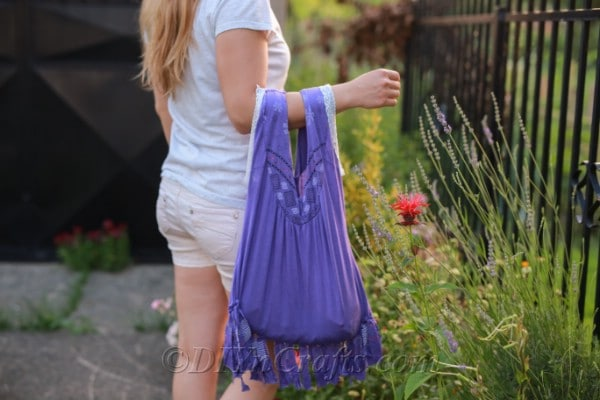 A woman carrying a bag made from an old T-shirt.