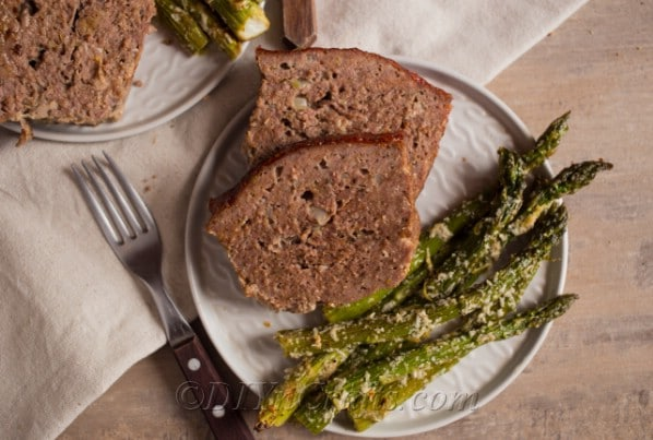glazed bbq meatloaf on a white plate being served with roasted parmesan asparagus