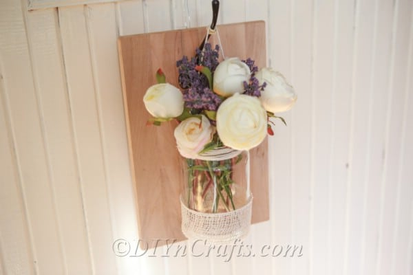 Finished rustic wall vase attached to wall, filled with flowers.
