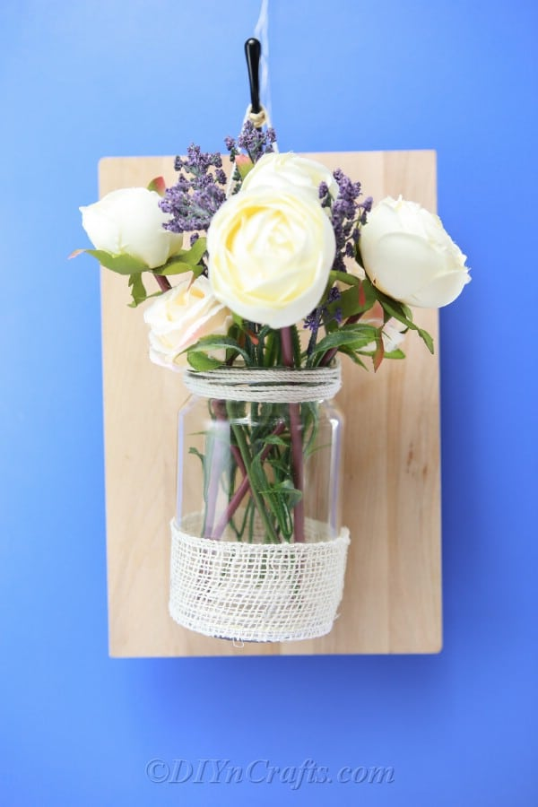 It is cheap and easy to make this rustic floral wall decor vase.
