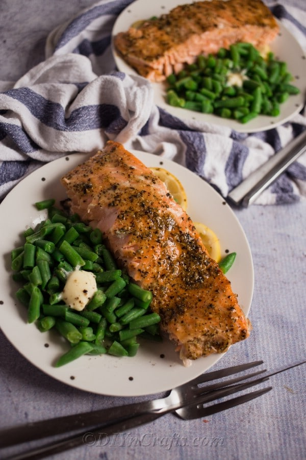 A place setting with two plates of baked salmon and green beans