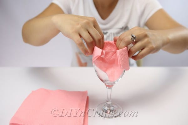 Folding a paper napkin over the top of a win glass when learning how to fold napkins