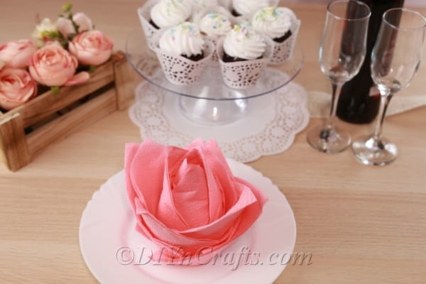 Picture of a flower napkin on a white plate in front of a cake stand with cupcakes and a bottle of wine