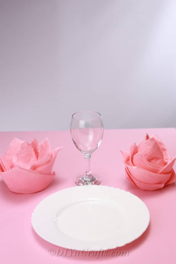 Finished napkin roses on a dinner table