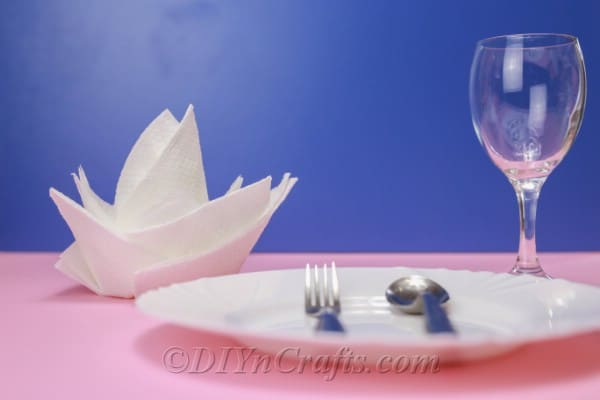 White flower napkin sitting on a pink tablecloth behind a white plate with a blue background