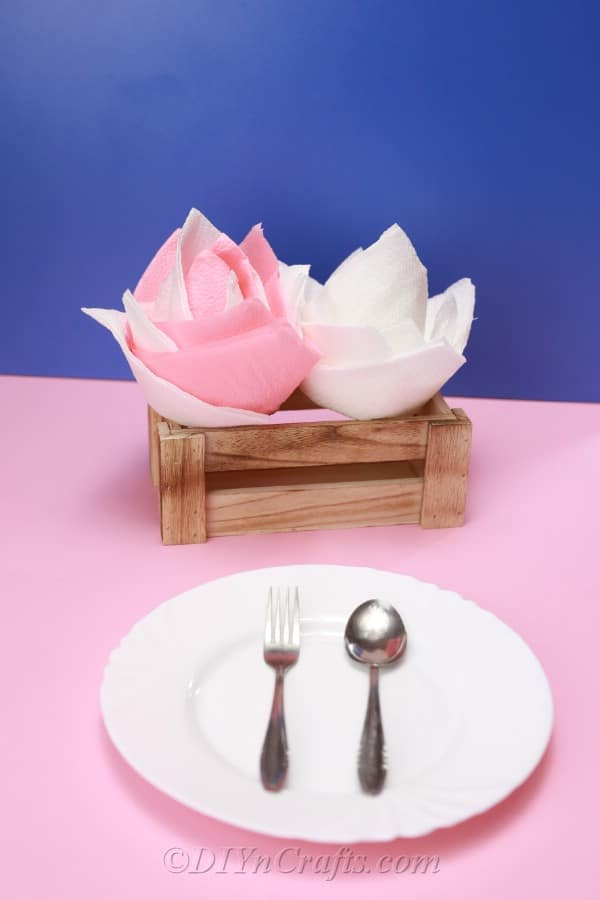 Two paper napkin flowers displayed beside a white plate that is sitting on a pink tablecloth