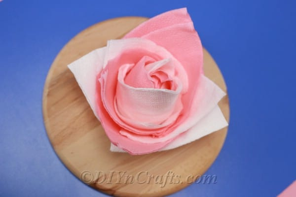 Overhead image of a paper napkin flower sitting on a wooden board on a blue surface created from the how to fold napkins tutorial