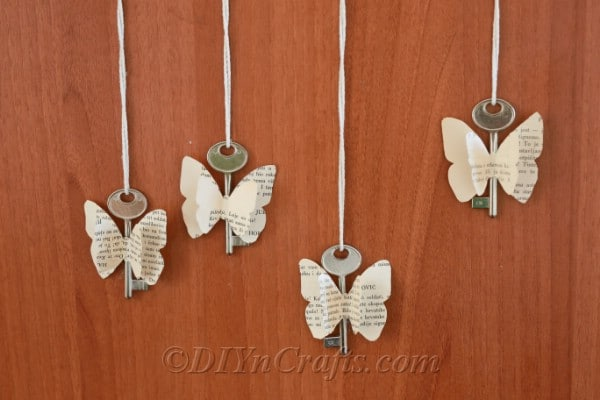 Rustic butterfly decorations made from old book pages and keys are displayed against a wood backdrop.
