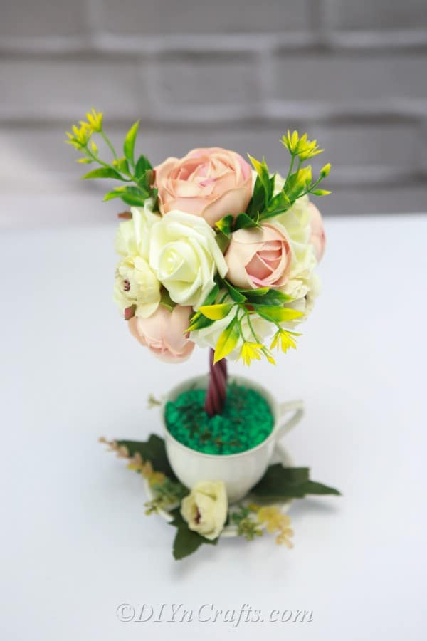 It is easy to make a flower arrangement topiary tree.