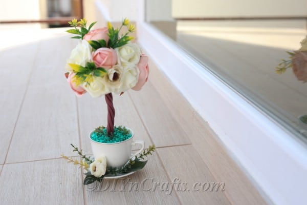 A topiary tree flower arrangement looks beautiful when complete.