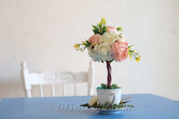 A topiary tree flower arrangement looks lovely on display.