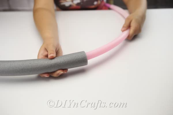 Stuff the hula-hoop inside the foam tube.