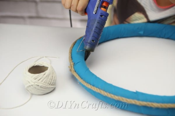 Use hot glue to attach string to the wreath.