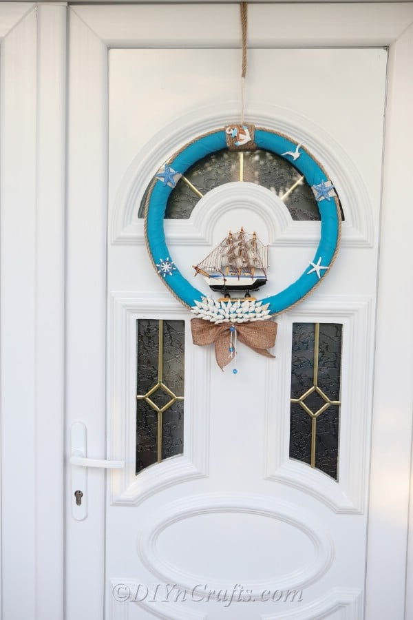 A completed nautical DIY wreath hanging on a door.