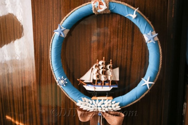 A nautical wreath hanging against wood.