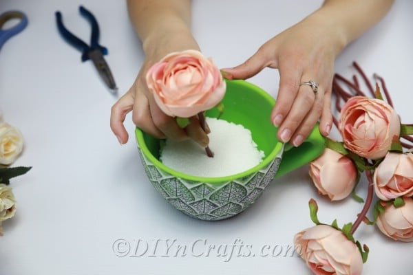 Arrange the flowers inside the teacup, pushing them down through the Styrofoam as you do.