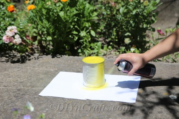 Tin can being sprayed yellow for bee craft outside on a white piece of paper