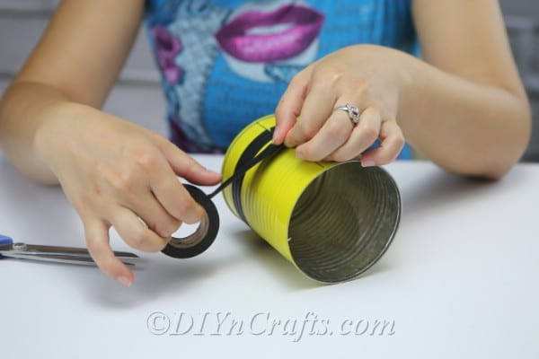 A picture showing a woman threading twine through holes to create legs on bee craft