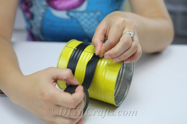"An image shows a woman threading a string through holes to create legs on a bee vehicle ""srcset ="" https://cdn.diyncrafts.com/wp-content/uploads/2019/08/tin-can-bee- IMG_8736.jpg 600w https://cdn.diyncrafts.com/wp-content/uploads/2019/08/tin-can-bee-IMG_8736-300x200.jpg 300w ""sizes ="" (maximum width: 600px) 100vw, 600px"