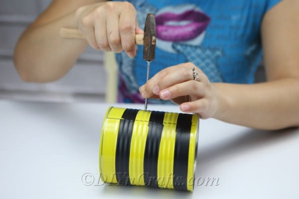 Making a hole in the tin can bee craft to add thread for hanging