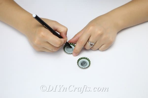 A woman drawing eyes inside bottle caps for the hanging bee craft