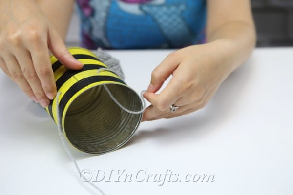 "An image showing a woman threading a string through holes to make legs on bee vehicles -can-bee-IMG_8750.jpg 600w, https://cdn.diyncrafts.com/wp-content/uploads/2019/08/ tin-can-bee-IMG_8750-300x200.jpg 300w ""sizes ="" (max-width: 600px) 100vw, 600px"
