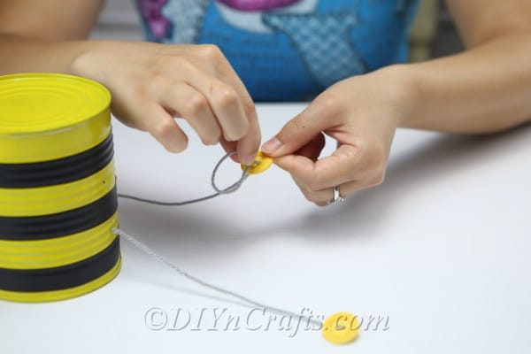 "Add buttons to the thread used for legs of the bee vehicle ""srcset ="" https://cdn.diyncrafts.com/wp-content/uploads/2019/08/tin-can-bee-IMG_8751.jpg 600w, https : / /cdn.diyncrafts.com/wp-content/uploads/2019/08/tin-can-bee-IMG_8751-300x200.jpg 300w ""sizes ="" (maximum width: 600px) 100vw, 600px"