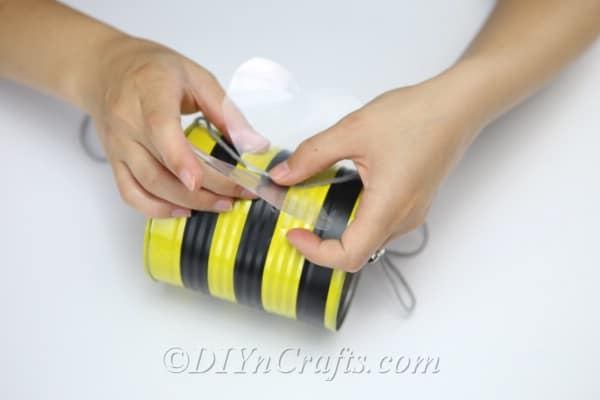 Attaching wings and hanging thread onto the tin can bee craft