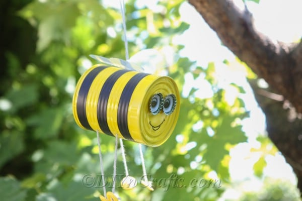 Cute hanging tin can bee decorating a garden.