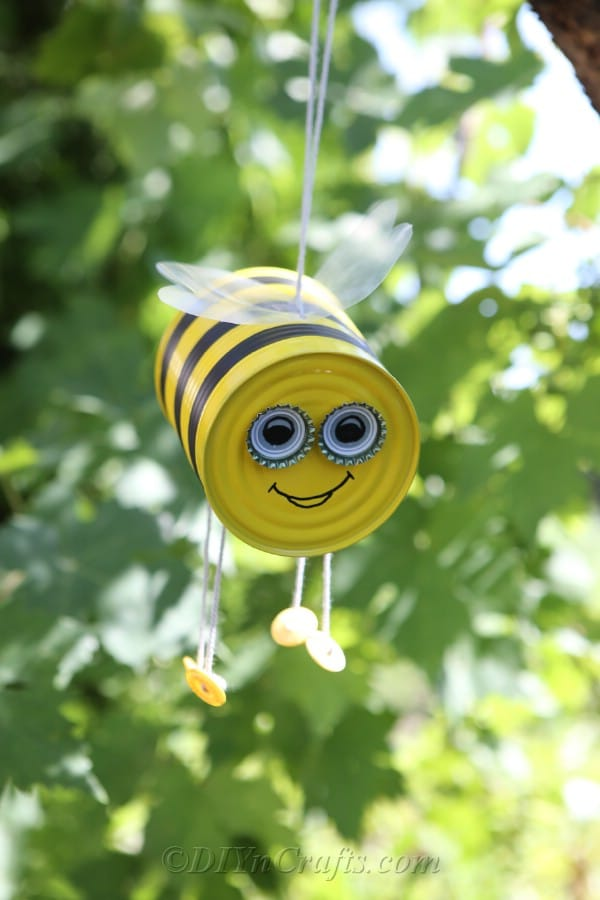 Tin can bee craft hanging from a tree