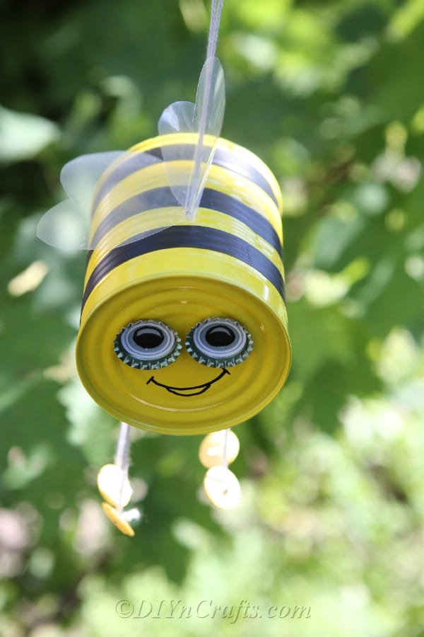 Up close picture of bee craft tin can hanging in a tree