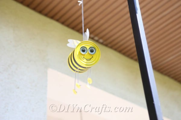 Tin can bee craft hanging from a porch