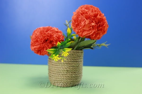 Tissue paper flowers in a basket against a blue backdrop.
