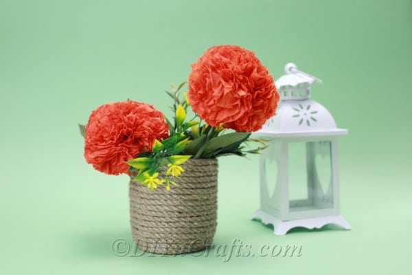 Tissue paper flowers are displayed in a basket with a simple green backdrop.