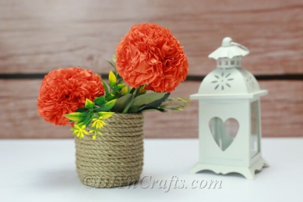 Tissue flowers arranged in a vase with a wooden rustic backdrop.
