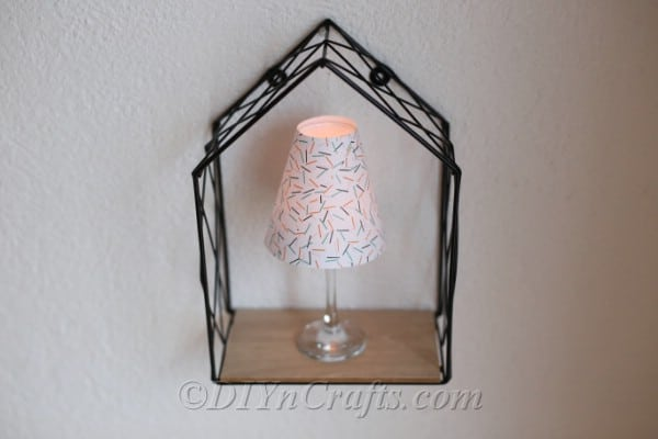 Decorative wine glass lantern sitting inside a wire frame box that is attached to a wall