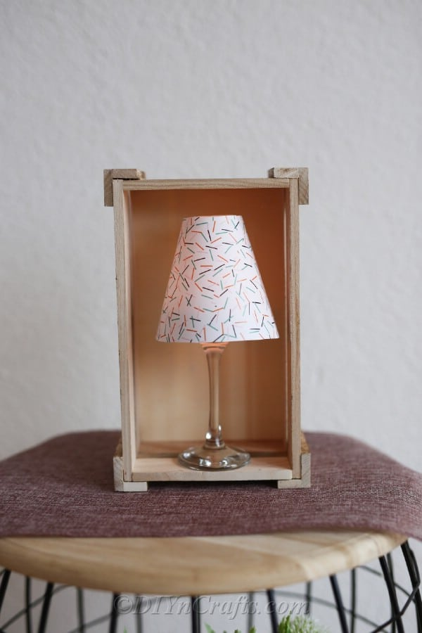 A prepared tealight candle holders paper wine glass lantern on a wooden stool with lamp sitting inside a decorative wooden box