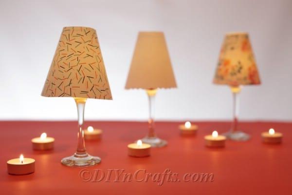 Wine glass lanterns on an orange table.