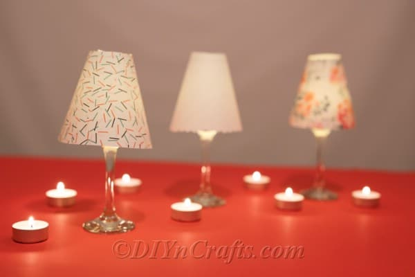 Three completed diy wine glass lantern tealight candle holders sitting on an orange table surrounded by lit candles